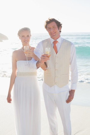 linking together: Happy newlyweds having champagne linking arms at the beach Stock Photo