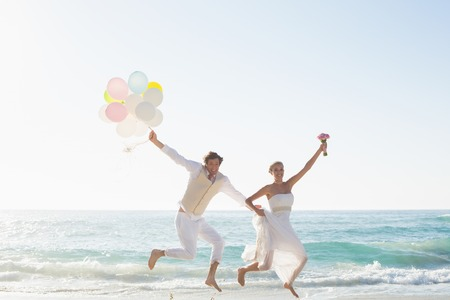 Newlyweds having fun holding balloons at the beach photo