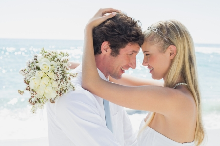 Romantic couple hugging on their wedding day at the beach photo