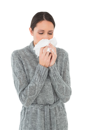 Casual young woman suffering from cold over white background photo