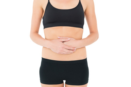 Close-up mid section of a fit young woman with stomach pain over white background