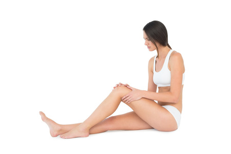 Side view of a fit young woman with knee pain sitting over white background photo