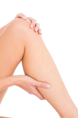 calf strain: Close-up mid section of a young woman with leg pain over white background