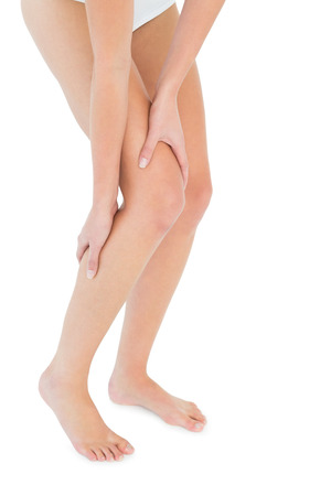 calf strain: Close-up low section of a fit young woman with leg pain over white background Stock Photo