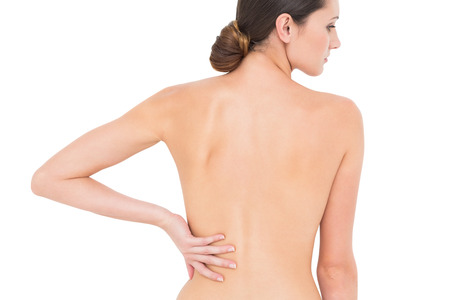 Rear view of a fit topless young woman with back pain standing over white background photo