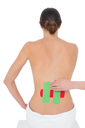 Rear view of a topless fit young woman with red and green strips on back over white background photo