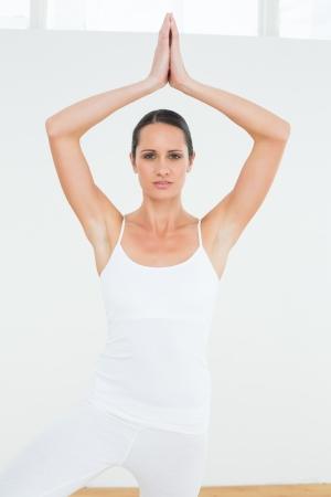 manos unidas: Retrato de una mujer joven deportiva con las manos juntas sobre la cabeza en un gimnasio