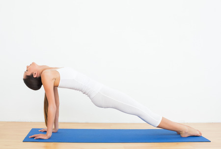 Full length of a fit young woman stretching body in the fitness studio photo