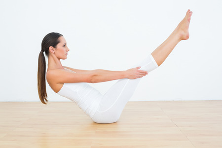 Full length side view of a toned young woman doing the boat pose in fitness studio Standard-Bild
