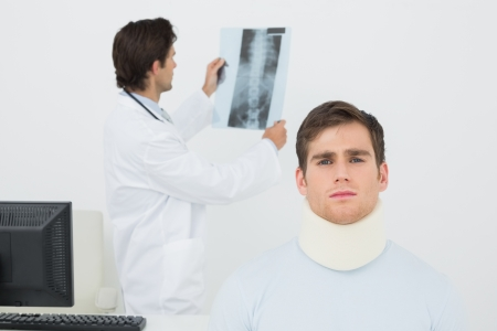 Patient in surgical collar with male doctor examining spine x-ray in background at medical office photo