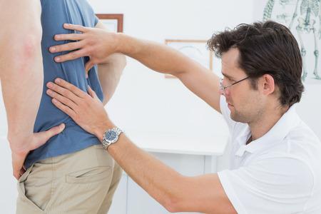 Seitenansicht Nahaufnahme eines männlichen Physiotherapeuten Prüfung mans wieder in der Arztpraxis