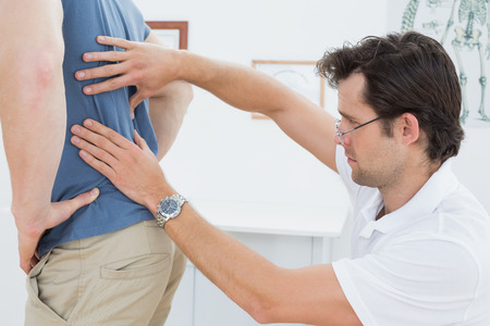 Side view close-up of a male physiotherapist examining mans back in the medical office photo