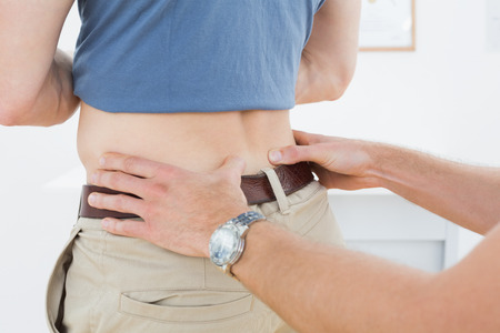 Close-up mid section of a physiotherapist examining mans back in the medical office photo