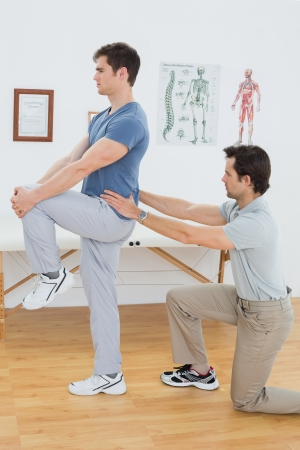 Side view of a male physiotherapist examining mans back in the medical office