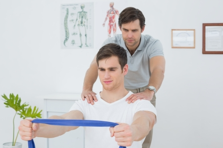 Male therapist assisting young man with exercises in the medical office photo
