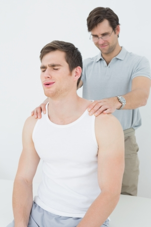 Male physiotherapist massaging a young mans shoulder in the medical office photo