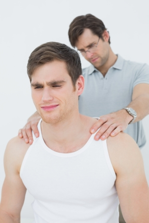 Male physiotherapist massaging a young mans shoulder over white background photo