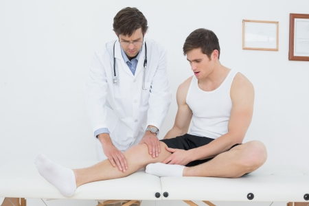 Full length of a young man getting his knee examined at the medical office photo