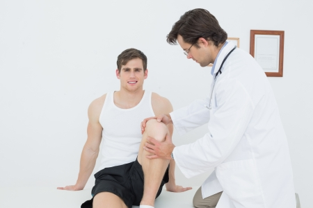Portrait of a smiling young man getting his knee examined at the medical office