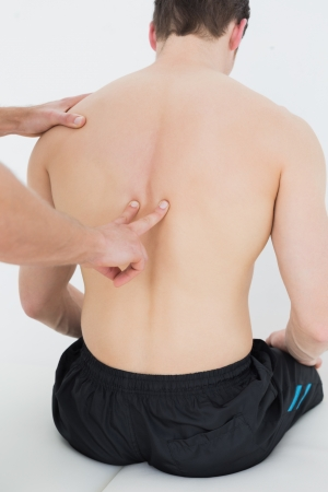 spinal manipulation: Vista posteriore di un uomo a torso nudo di essere massaggiato da un fisioterapista su sfondo bianco