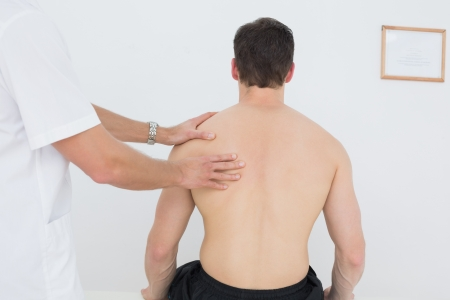 Rear view of a shirtless man being massaged by a physiotherapist over white background photo