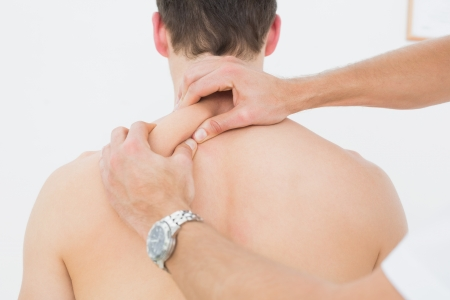 Close-up rear view of a shirtless man being massaged by a physiotherapist over white background photo