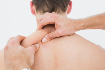 massaged: Close-up rear view of a shirtless man being massaged by a physiotherapist over white background
