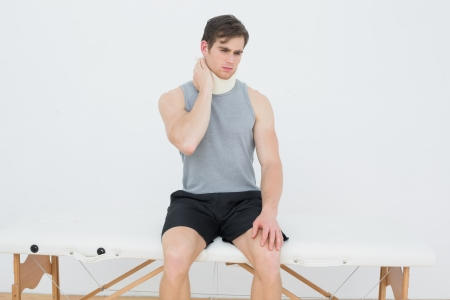 Handsome young man wearing cervical collar in the medical office photo