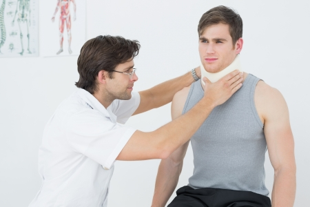 Male doctor examining a patients neck in the medical office photo