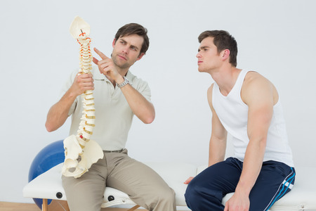 Male physiotherapist showing patient something on skeleton model in medical office photo