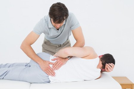 Male physiotherapist examining mans back in the medical office Stock Photo