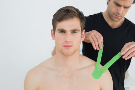 Male physiotherapist putting on green kinesio tape on patients shoulder in the medical office