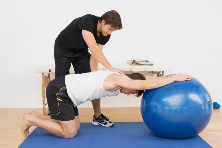 physical therapist: Physical therapist assisting young man with yoga ball in the gym at hospital Stock Photo
