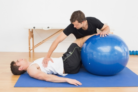 Physical therapist assisting young man with yoga ball in the gym at hospital Stock Photo