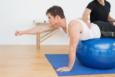 yoga to cure health: Physical therapist assisting young man with yoga ball in the gym at hospital Stock Photo