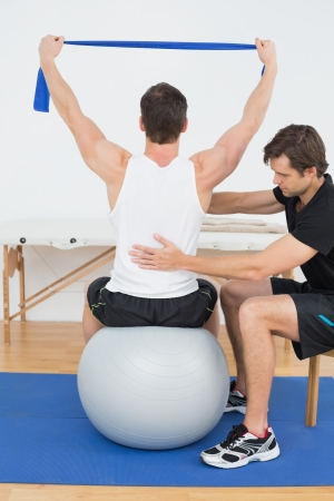Young man sitting on yoga ball while working with a physical therapist