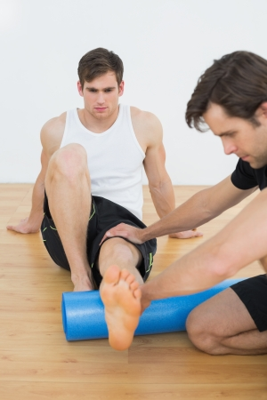 Physical therapist examining a young mans leg at the hospital gym Stock Photo