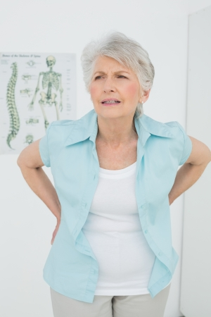 Senior woman with back pain standing in the medical office photo