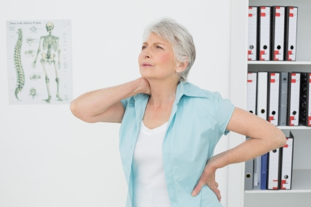 Senior woman suffering from neck pain standing in the medical office Stock Photo