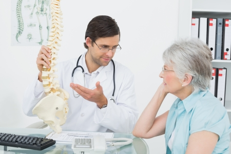 Male doctor explaining the spine to a senior patient in medical office photo