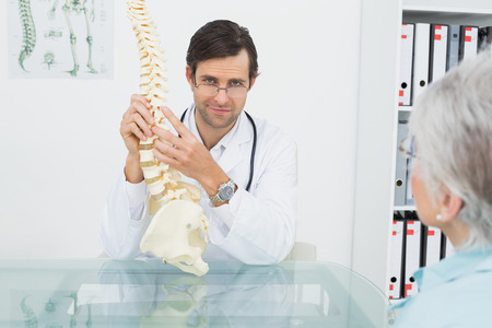 Portrait of a male doctor explaining the spine to a senior patient in medical office photo