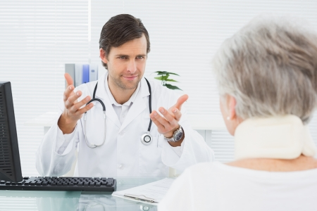 Smiling male doctor listening to senior patient with concentration at the medical office photo