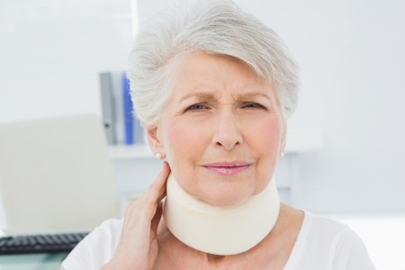 Portrait of a senior woman wearing cervical collar in the medical office photo