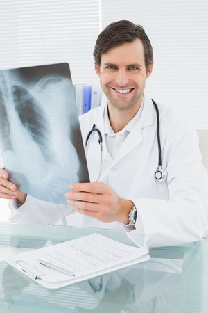 Portrait of a smiling male doctor with lungs x-ray in the medical office photo