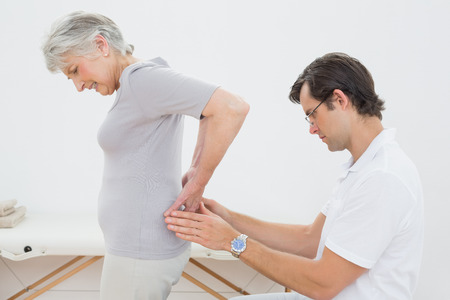 Side view of a male physiotherapist examining senior womans back in the medical office