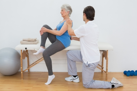 Male physiotherapist examining senior womans back in the medical office