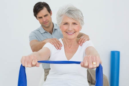 Male therapist assisting senior woman with exercises in the medical office photo