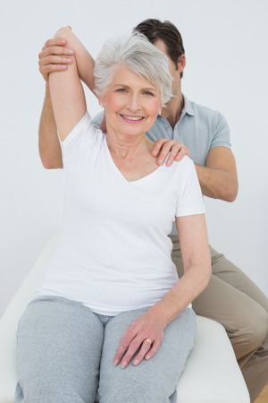 Male physiotherapist stretching a smiling senior woman's arm in the medical office