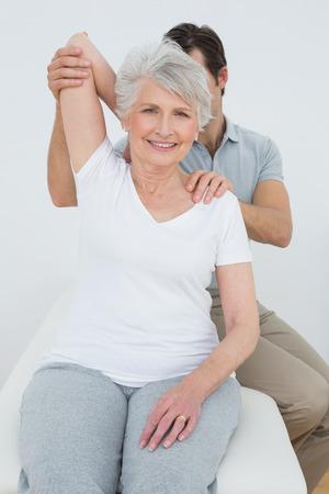 Männlich Physiotherapeut Strecken einer lächelnde ältere Frau am Arm in der Arztpraxis