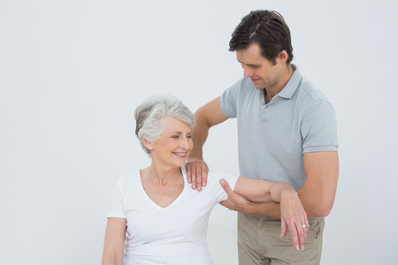 physical pressure: Male physiotherapist massaging a smiling senior womans arm in the medical office